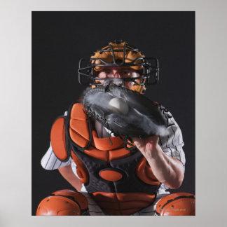Baseball catcher holding ball in mitt poster