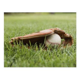 Baseball mitt with ball in grass postcard
