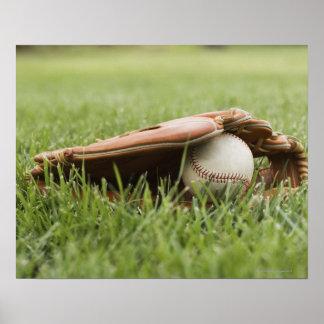 Baseball mitt with ball in grass poster