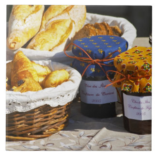 Basket with croissants and chocolate breads. large square tile