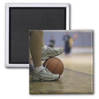 Basketball player holding ball with feet fridge magnet