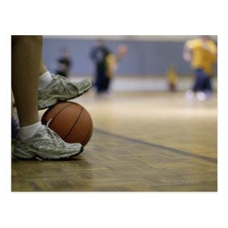 Basketball player holding ball with feet postcard