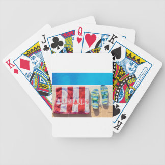 Bathing slippers and bath towel at swimming pool bicycle playing cards
