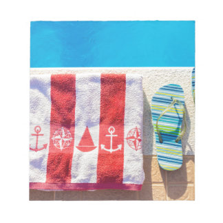 Bathing slippers and bath towel at swimming pool notepads