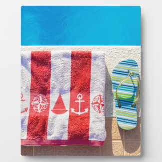 Bathing slippers and bath towel at swimming pool plaque