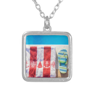 Bathing slippers and bath towel at swimming pool silver plated necklace