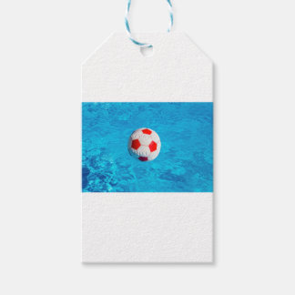Beach ball floating  in blue swimming pool gift tags