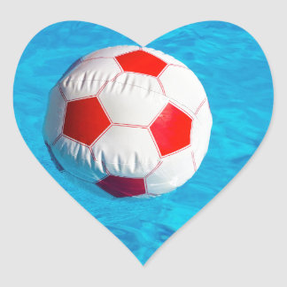 Beach ball floating  in blue swimming pool heart sticker