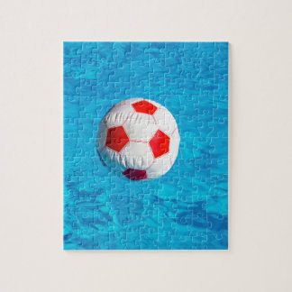 Beach ball floating  in blue swimming pool jigsaw puzzle