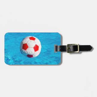 Beach ball floating  in blue swimming pool luggage tag