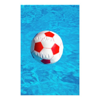 Beach ball floating  in blue swimming pool stationery