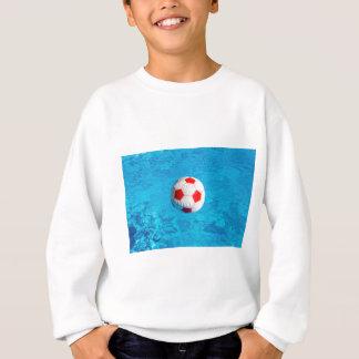 Beach ball floating  in blue swimming pool sweatshirt