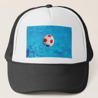 Beach ball floating  in blue swimming pool trucker hat