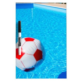 Beach ball floating on water in swimming pool dry erase board