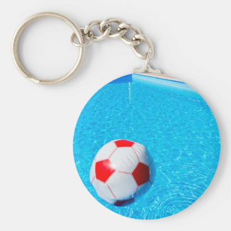 Beach ball floating on water in swimming pool key ring