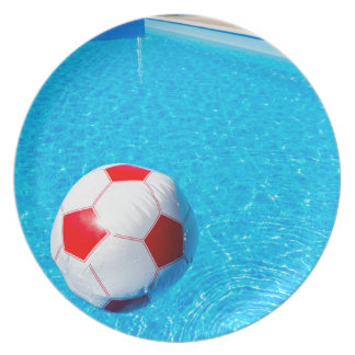 Beach ball floating on water in swimming pool plate