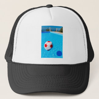 Beach ball floating on water in swimming pool trucker hat
