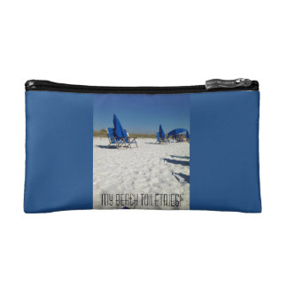 beach scene of sand and blue skies and chairs cosmetics bags
