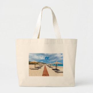 Beach umbrellas and loungers at greek sea large tote bag