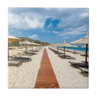 Beach umbrellas and loungers at greek sea small square tile