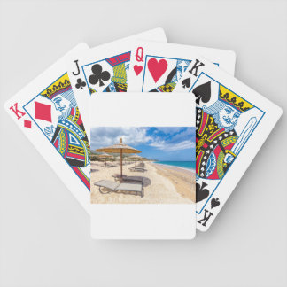 Beach umbrellas in rows on sandy beach with sea bicycle playing cards
