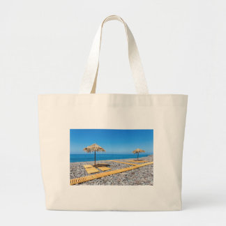 Beach umbrellas with path and stones at coast large tote bag