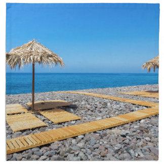 Beach umbrellas with path and stones at coast napkin