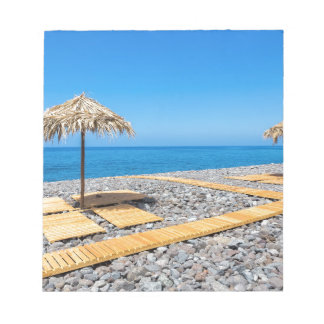 Beach umbrellas with path and stones at coast notepad