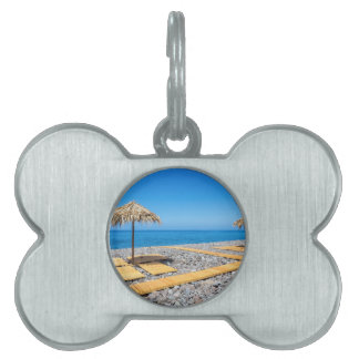 Beach umbrellas with path and stones at coast pet name tag