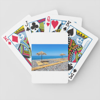 Beach umbrellas with path and stones at coast poker deck