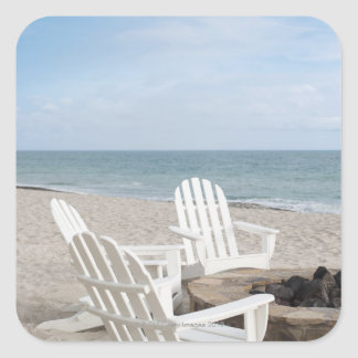 beachfront house with adirondack chairs and square sticker
