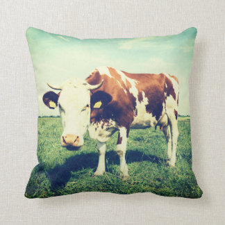 Beautiful pillow with a cow on a field