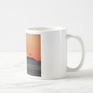 Beautiful sea sunset with island silhouette coffee mug