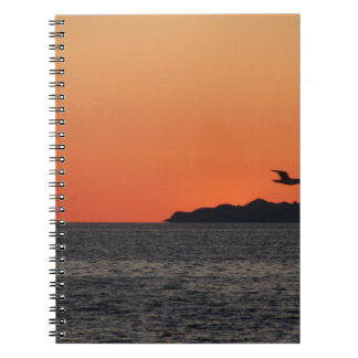 Beautiful sea sunset with island silhouette notebook