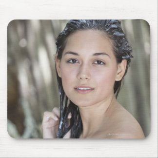 Beautiful young woman wrapped in towel and mouse pad