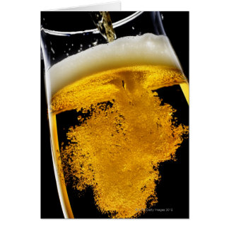 Beer been poured into glass, studio shot card