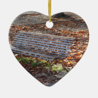 Bench in autumn park with dead leaves ceramic heart decoration