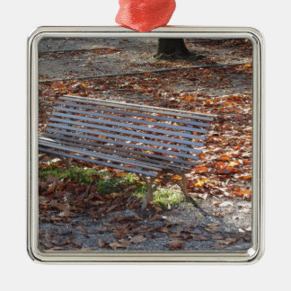 Bench in autumn park with dead leaves metal ornament