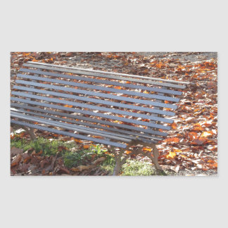 Bench in autumn park with dead leaves rectangular sticker