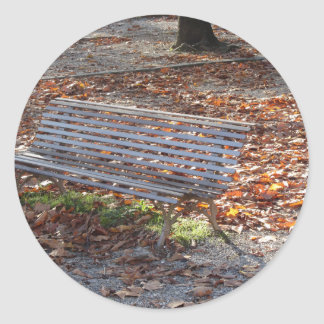 Bench in autumn park with dead leaves round sticker