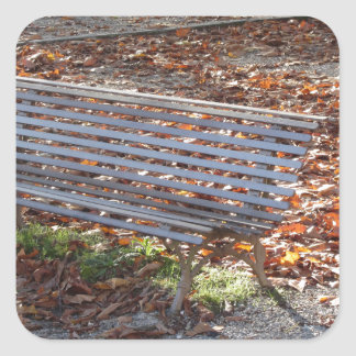 Bench in autumn park with dead leaves square sticker