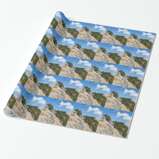 Bench on rocky mountain with trees and blue sky