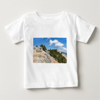 Bench on rocky mountain with trees and blue sky baby T-Shirt