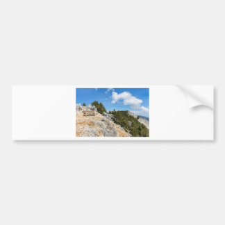Bench on rocky mountain with trees and blue sky bumper sticker