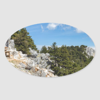 Bench on rocky mountain with trees and blue sky oval sticker
