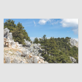 Bench on rocky mountain with trees and blue sky rectangular sticker