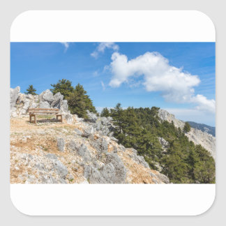 Bench on rocky mountain with trees and blue sky square sticker