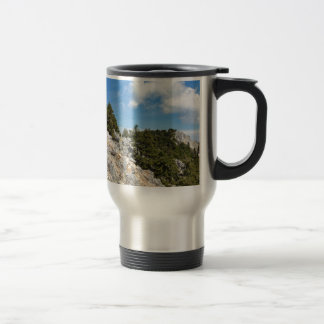 Bench on rocky mountain with trees and blue sky travel mug