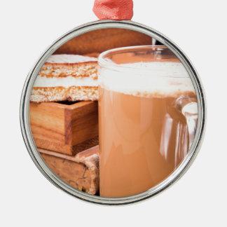 Big mug of hot cocoa with foam metal ornament