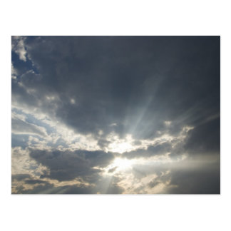 Big rays of light with many clouds and blue sky post card